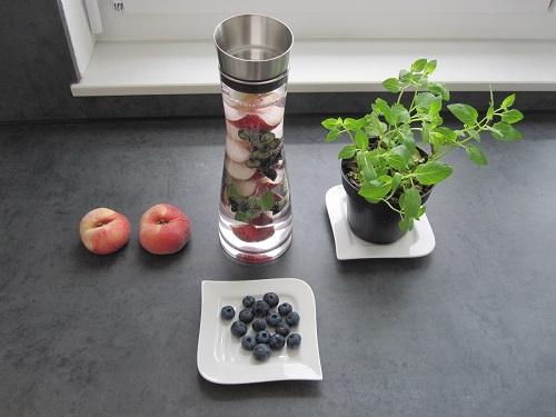 aromatisiertes wasser mit plattpfirsichen heidelbeeren und minze wasser. Black Bedroom Furniture Sets. Home Design Ideas